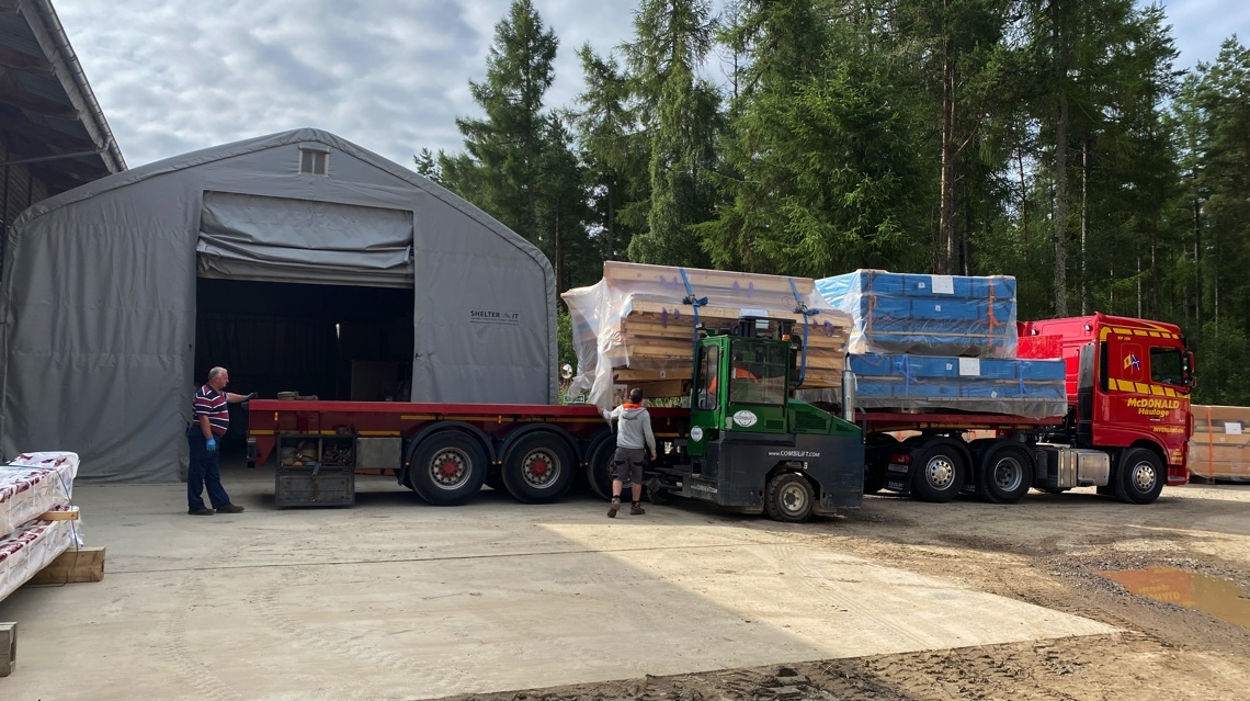 n-SIPs and other components for an eco kit house being loaded for transport